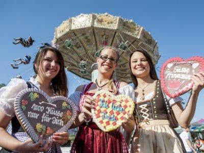 3 Frauen im Dirndl mit Lebkuchenherzen, im Hintergrund Kettenkarussell