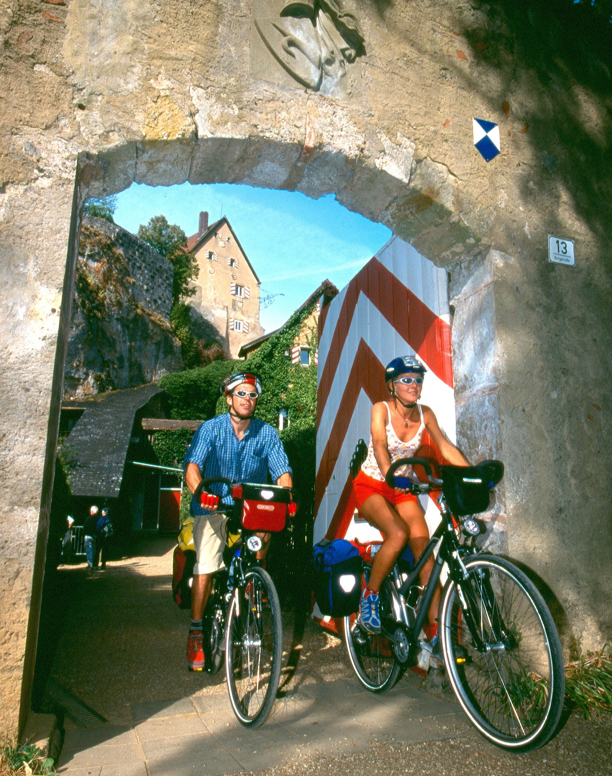 Radlerpaaar fährt durch das Tor der Burg Pottenstein