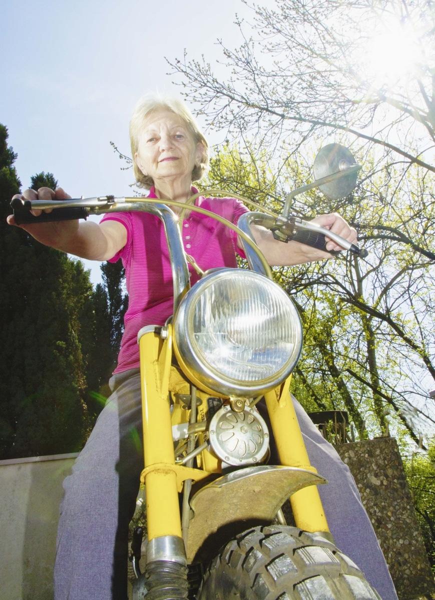 Ältere Dame auf Motorrad