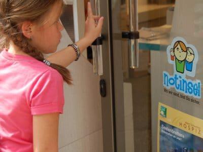 Mädchen öffnet Ladentür, auf der Notinsel steht
