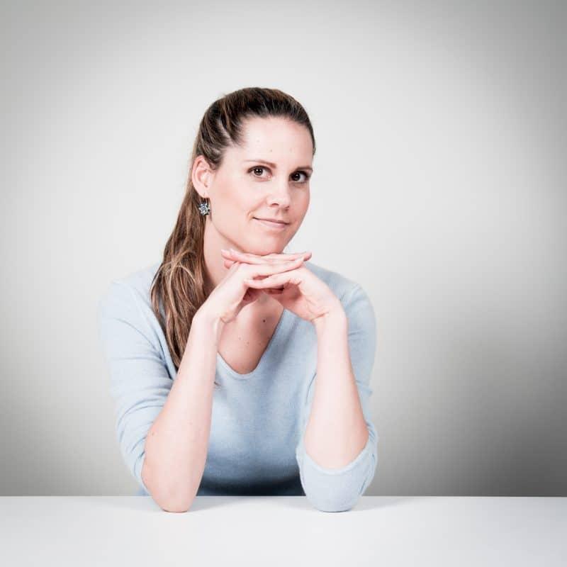 Frau mit langen Haaren und hellblauem Oberteil vor grauem Hintergrund