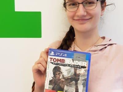 Junge Frau mit Brille hält ein Computerspiel und lacht