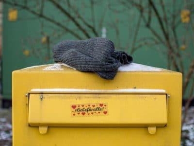 gelber Briefkasten mit grauer Mütze darauf