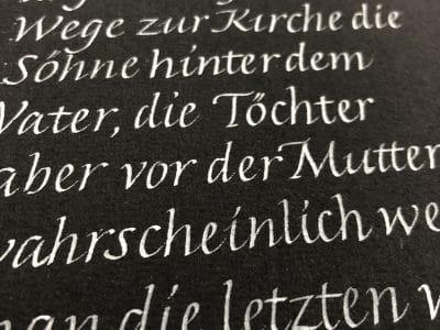 weiße Schrift in Kalligraphie auf schwarzem Hintergrund