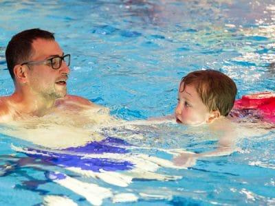 Ein Mann schwimmt mit einem kleinen Kind im Wasser.