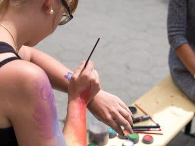 Frau sitzend bemalt ihren Arm mit Farbe