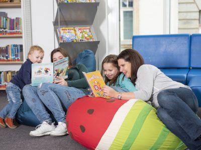 Frauen und Kinder sitzen auf Sitzsack und lesen