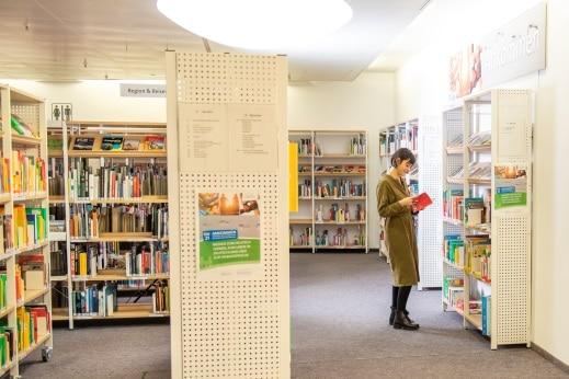 Mitarbeiterin vor weißem Bücherregal