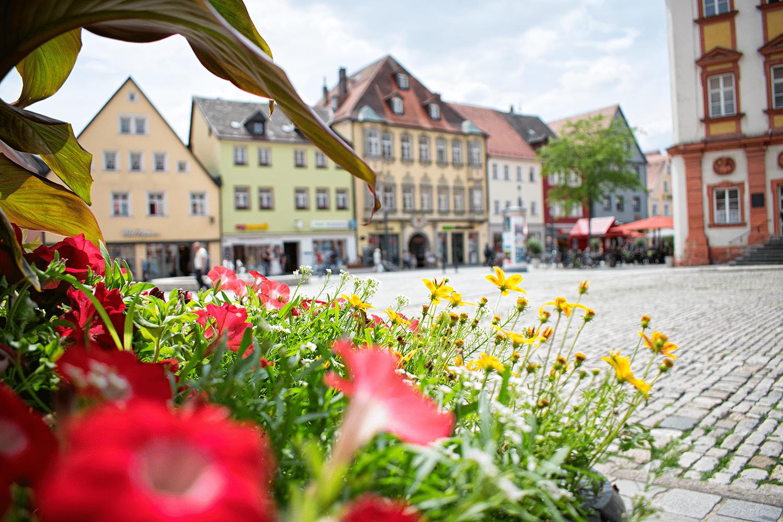 Blick in die Fußgängerzone mit Blumentrog im Vordergrund.