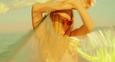 blonde Frau mit roter Sonnenbrille tanzt im Sonnenschein