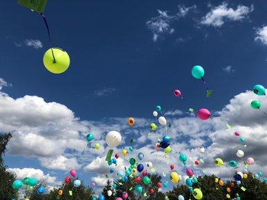 Bunte Luftballons steigen in den blauen Himmel.