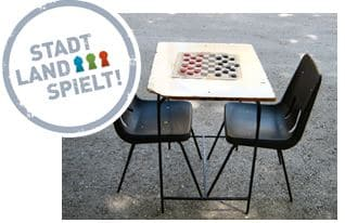 Tisch mit Spiel darauf und Stühle dazu