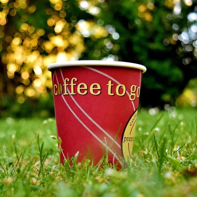Ein Einweg-Kaffeebecher auf der Wiese