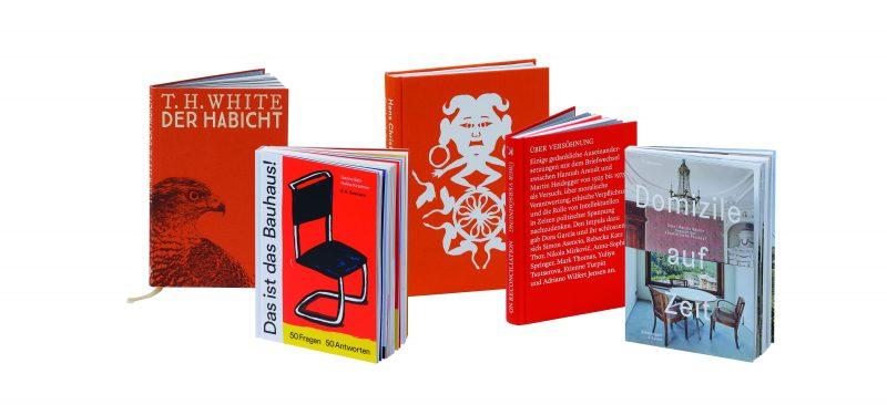Rote Bücher stehen vor weißem Grund