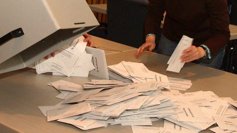 Stimmzettel werden aus einer Urne ausgeschüttet.