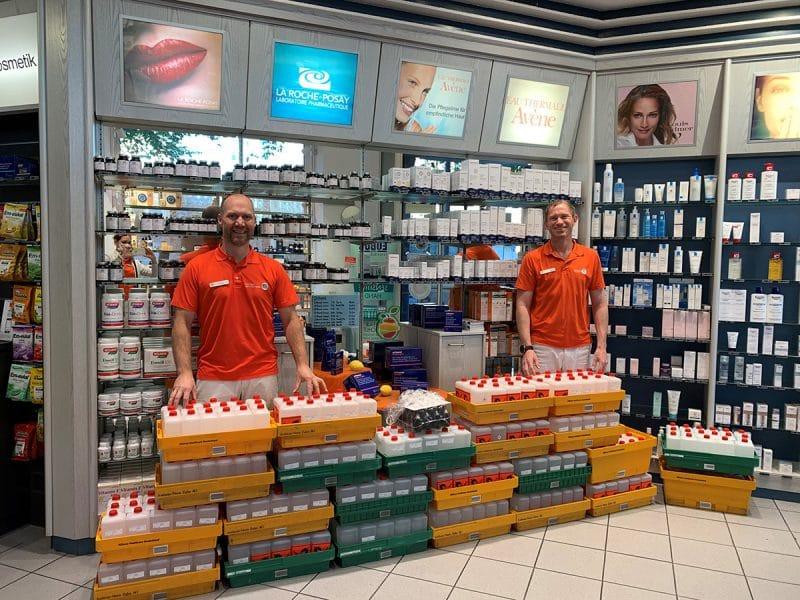 Dr. Jens Landwehr (rechts) und Dr. Andreas Paul von der Rathaus-Apotheke mit den 400 Litern Handdesinfektionsmitteln.