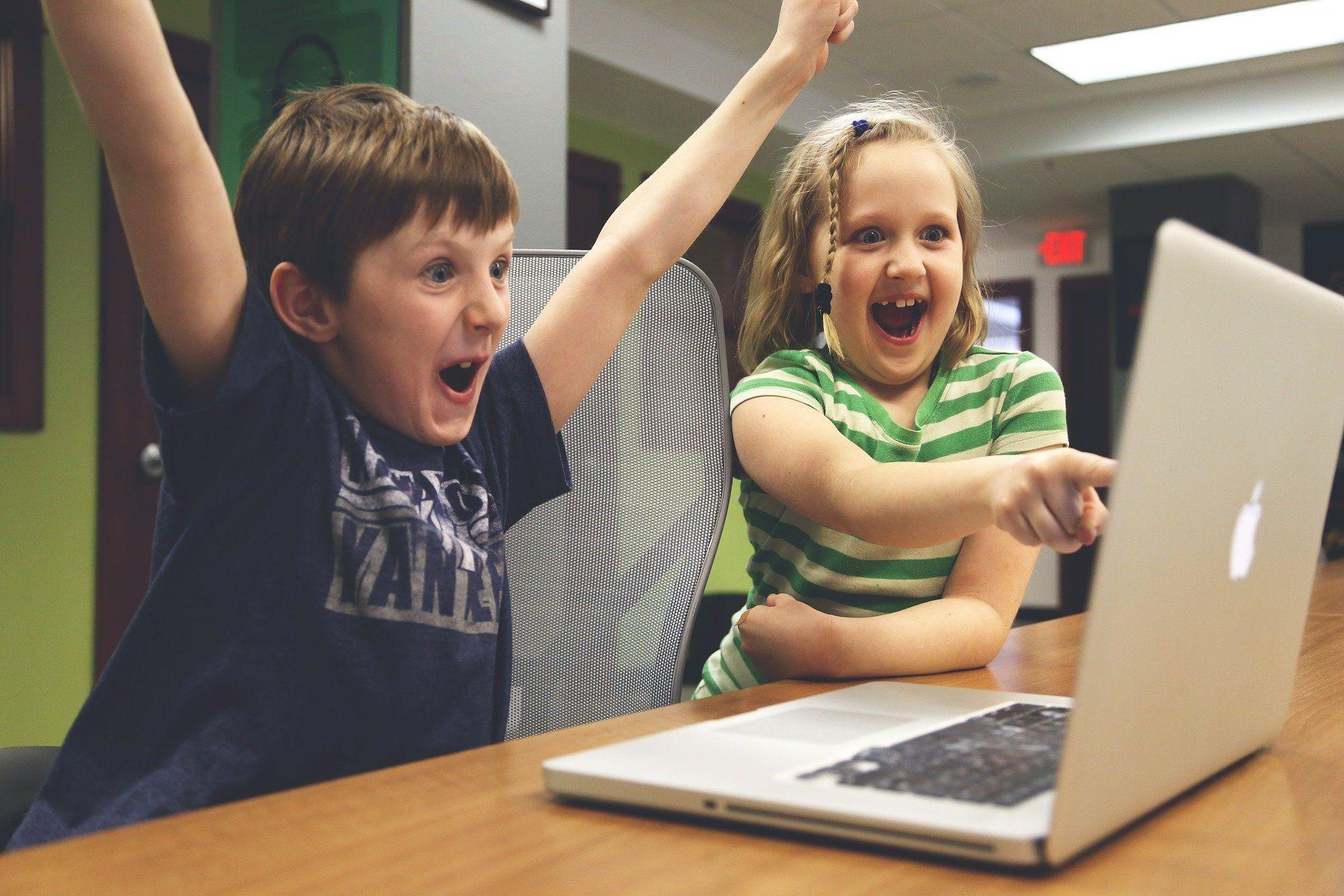 Zwei Kinder sitzen vor einem Laptop