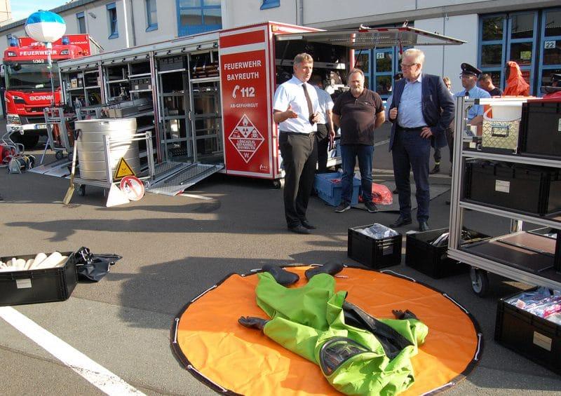 Stadtbrandrat Ralph Herrmann (links) erklärt Oberbürgermeister Thomas Ebersberger (rechts) und Stadtrat und Feuerwehrpfleger Thomas Bauske den Inhalt des neuen Abrollbehälters Gefahrengut.
