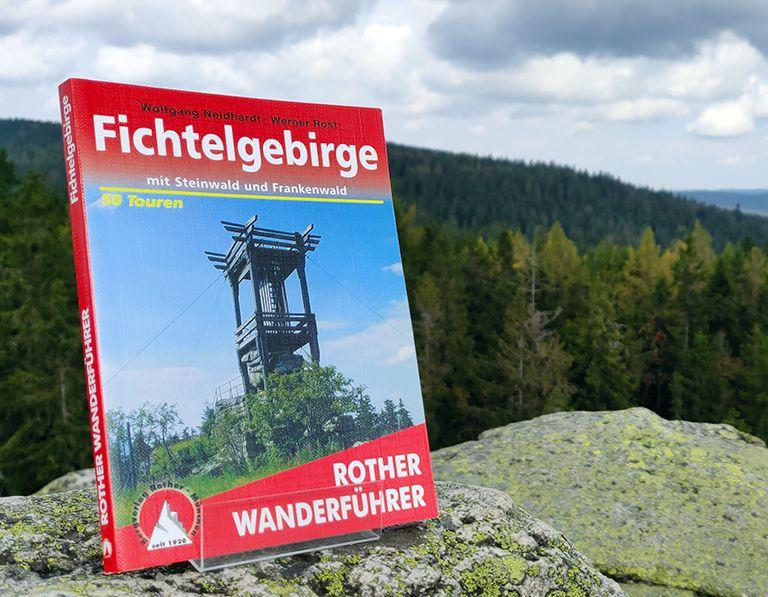 Buch steht auf einem Stein im Gebirge.