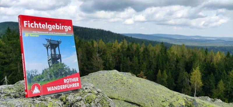 Ein Buch steht auf Berggipfelmit Blick ins Fichtelgebirge