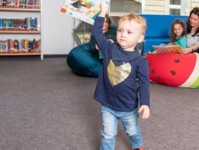 Kleinkind hält Buch in der Bibliothek.