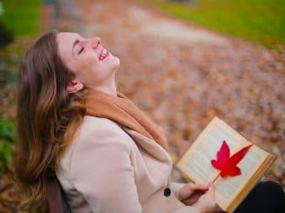 Lachende Frau mit einem Buch in der Hand.