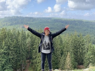 Eine Frau steht mit ausgebreiteten Armen auf einem Berg.