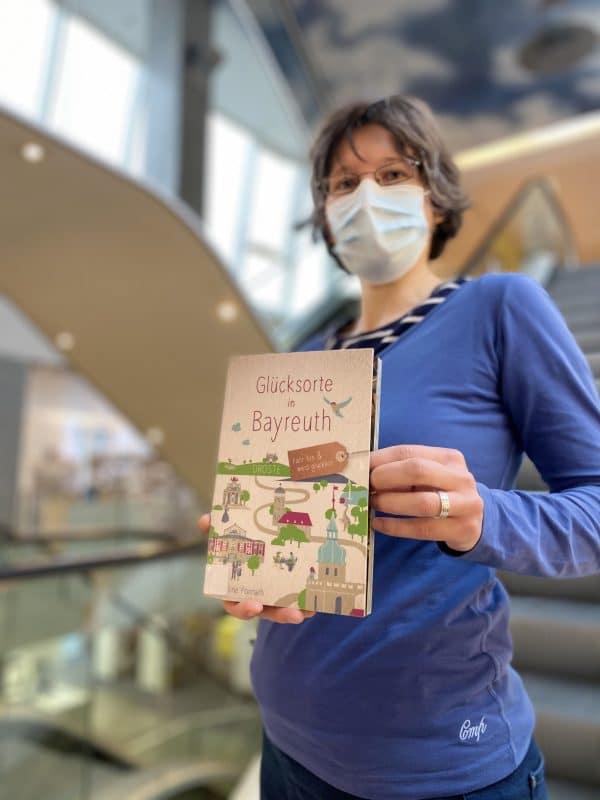 """Eine Frau zeigt Buch """"Glücksorte in Bayreuth"""""""