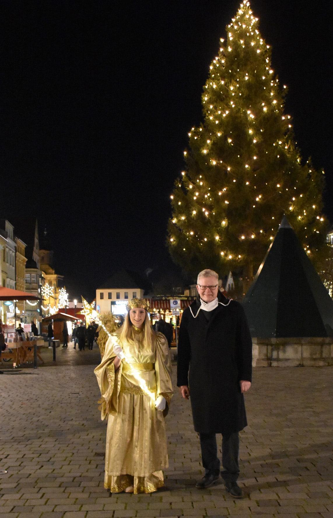 Christkind Nike Hellbach mit OB Ebersberger vor einem beleuchteten Weihnachtsbaum.n