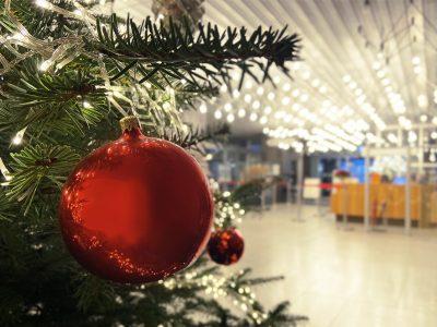 Eine rote Christbaumkugel hängt am Ast eines Weihnachtsbaums.