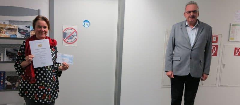 Die Abteilungsleiterin Soziale Dienste Bettina Wurzel zeigt die Urkunde des Integrationspreises.