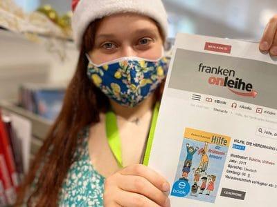 Junge Frau mit Nikolausmütze hält Zettel hoch