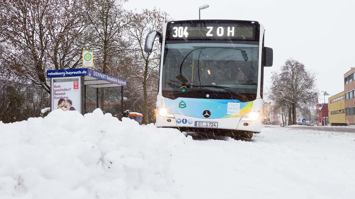 Stadtbus auf schneebedeckter Straße.