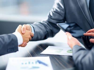 Zwei Menschen reichen sich die Hände zum Vertragsabschluss
