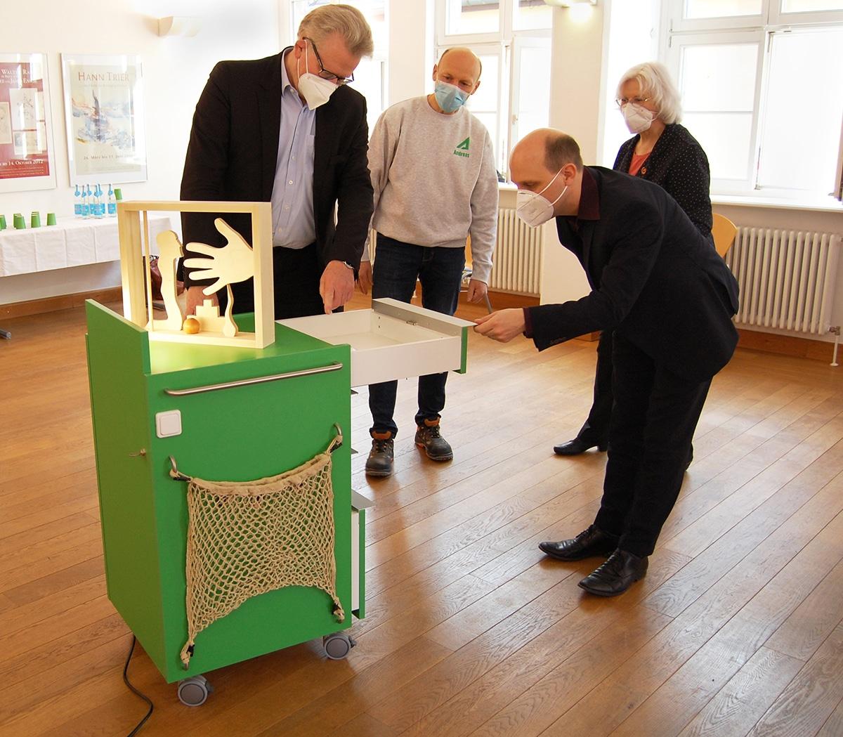 Oberbürgermeister Thomas Ebersberger (links) und Kulturreferent Benedikt Stegmayer erkunden den neuen Inklusions-Trolley für das Kunstmuseum. Museumsleiterin Dr. Marina von Assel und Schreiner Andreas Angermann erklären die einzelnen Funktionen.
