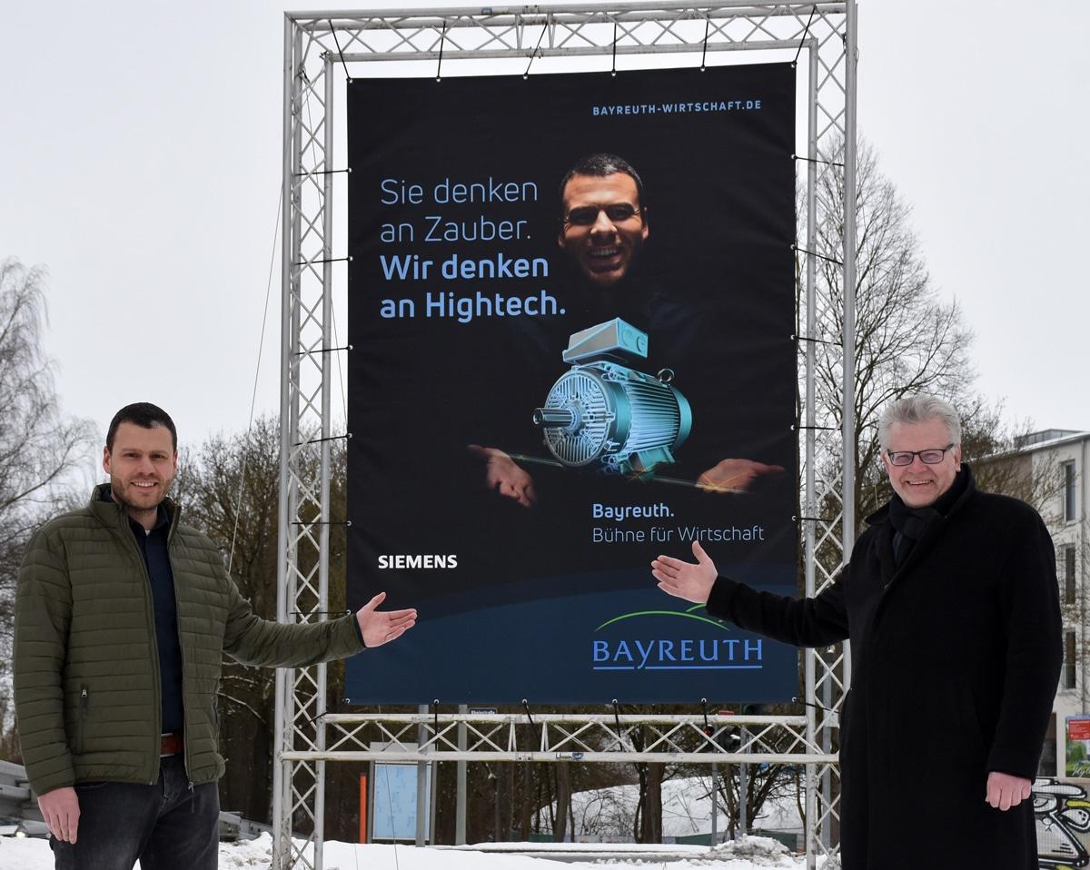 """Hartmut Oltsch und Oberbürgermeister Ebersberger vor einer Großplakatwand der Kampagne """"Bayreuth. Bühne für Wirtschaft""""."""