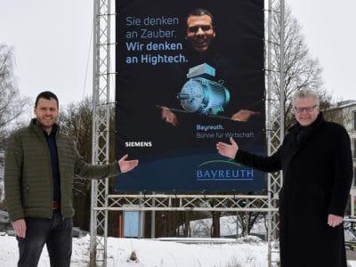 """Dominik Herrmann (Siemens) und Oberbürgermeister Ebersberger vor einer Plakatwand der Kampagne """"Bayreuth. Bühne für Wirtschaft""""."""