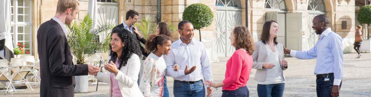 Neue Bürgerinnen und Bürger im Gespräch vor dem Opernhaus