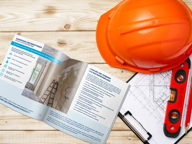 Broschüre des Leerstandsmanagements liegt neben Plänen und Handwerkergeräten
