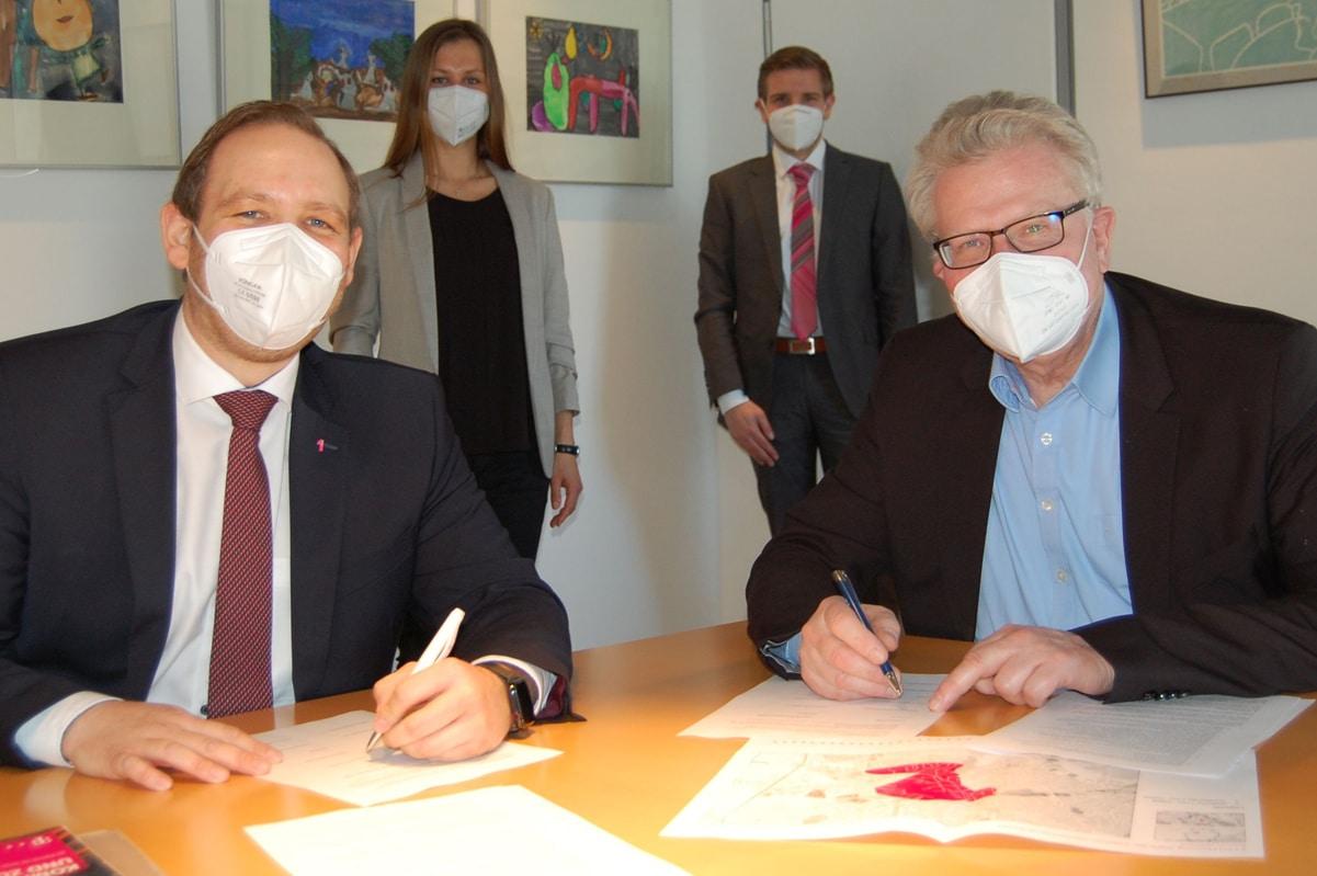 Oberbürgermeister Thomas Ebersberger (rechts) und Enrico Delfino unterzeichnen die Absichtserklärung. Im Hintergrund Svenja Herrmann, KeyAccountManager Breitbandausbau, und Jens Kolodzig, Teamleiter Rolloutoffice (beide Telekom).