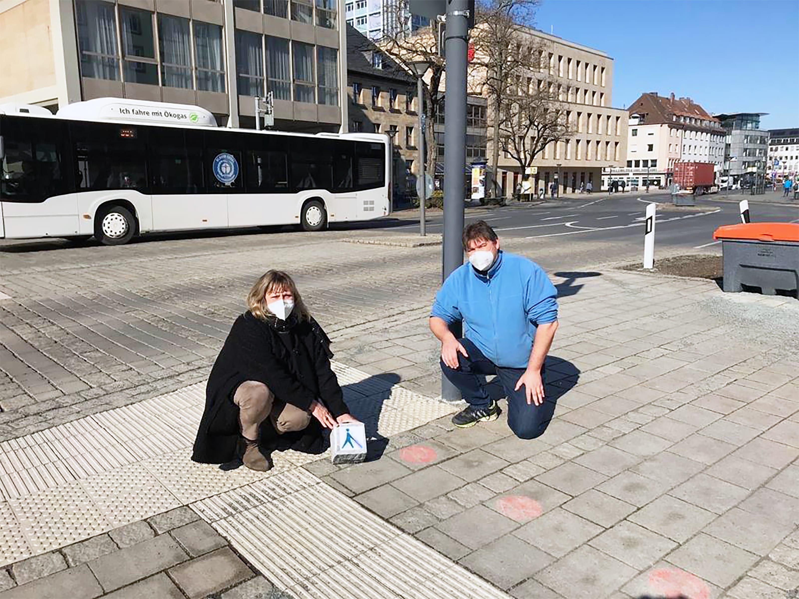 Margit Lebershausen (Fachstelle Inklusion) und Axel Höhmann (Mitglied des Behindertenbeirates) zeigen das Blindenlogo, das aufgesprüht werden soll