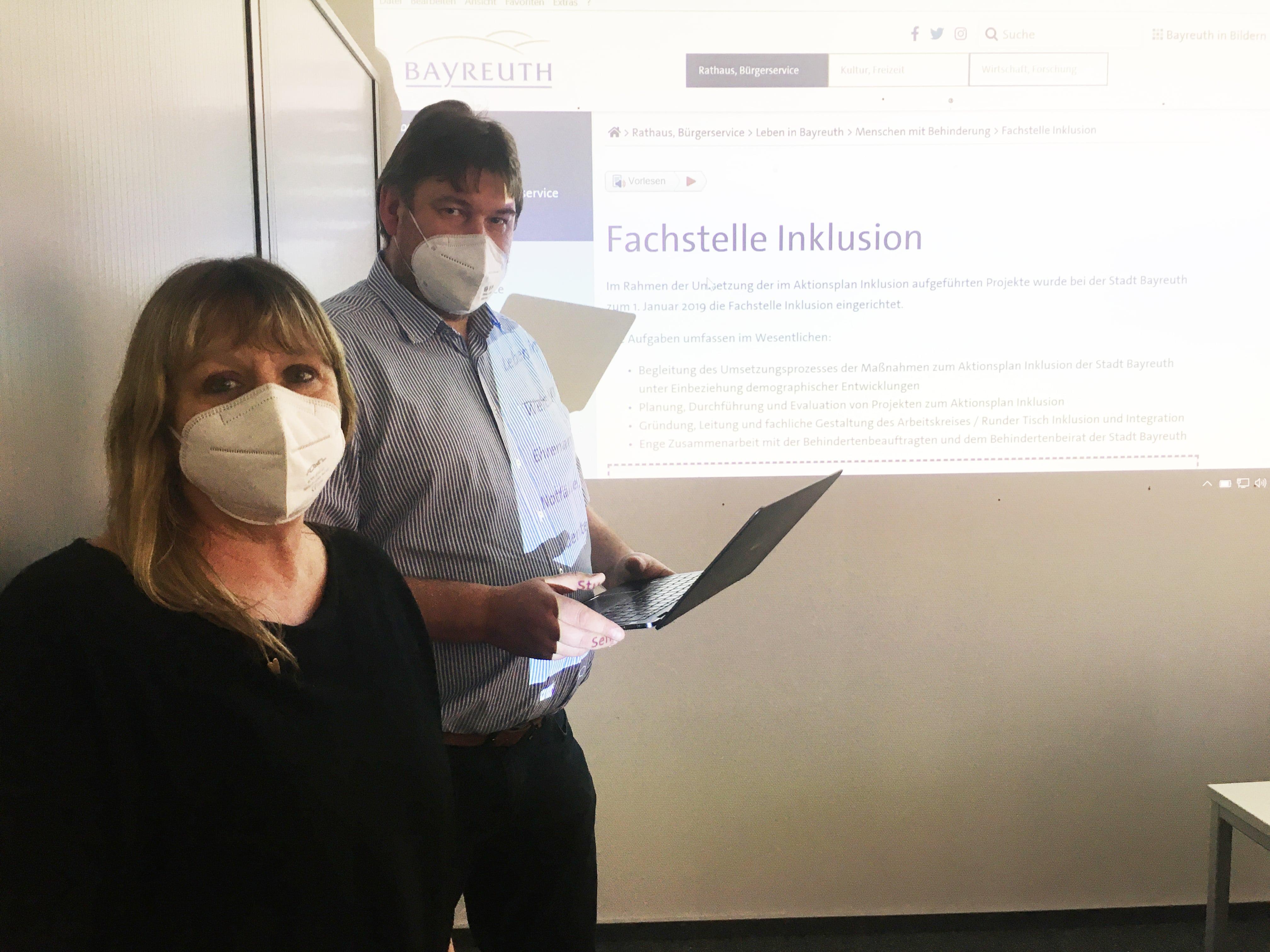 Frau Lebershausen (Fachstelle Inklusion) und Herr Höhmann (Mitglied des Behindertenbeirates) stehend vor Leinwand mit Bild der Homepage der Fachstelle Inklusion im Hintergrund.