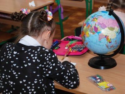 Mädchen sitzt am Schultisch mit Globus