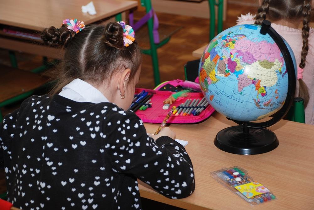 Mädchen sitz Schultisch mit Globus