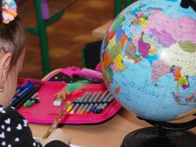 Ein Mädchen sitz am Schultisch mit Globus