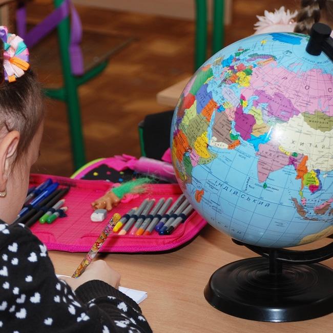 Ein Mädchen sitzt am Schultisch mit Globus