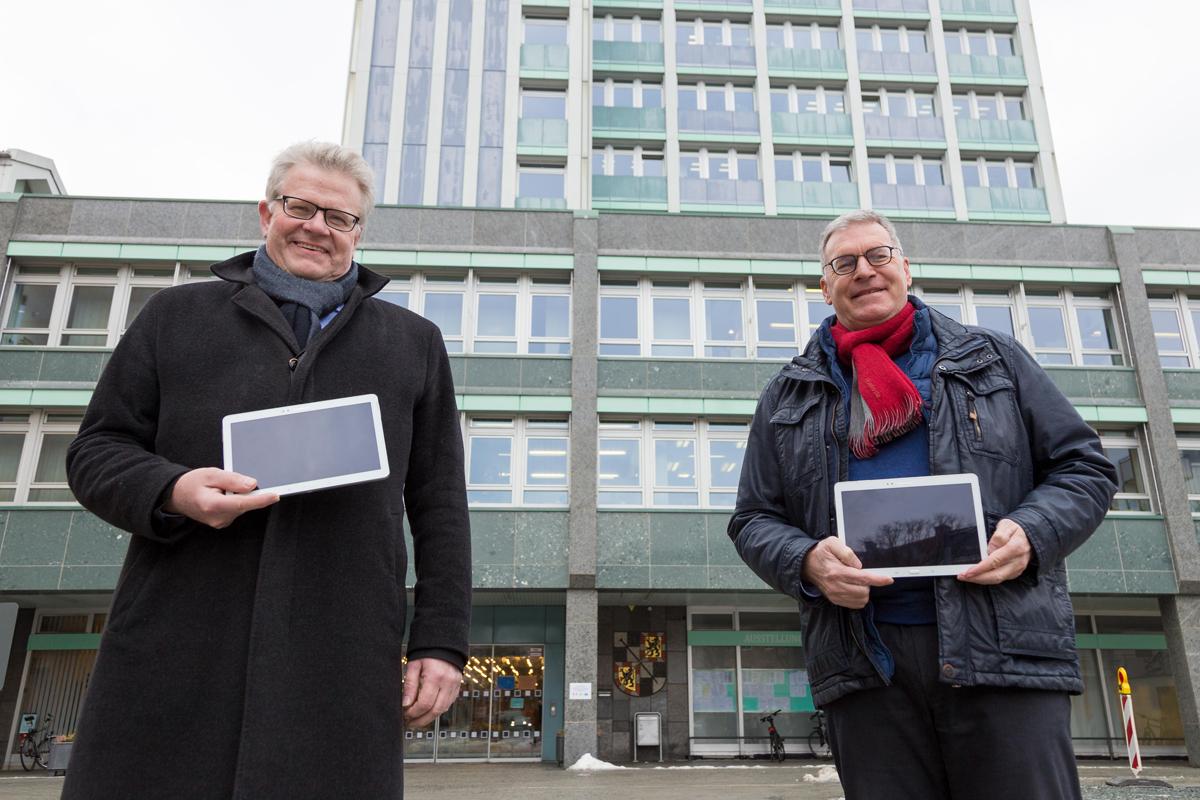 Oberbürgermeister Thomas Ebersberger und Jürgen Bayer von den Stadtwerken mit Tablets vor dem Rathaus.