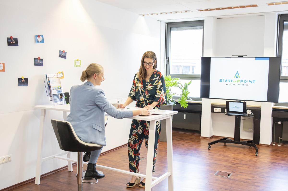 Büroraum mit zwei jungen Frauen an einem Besprechungstisch.