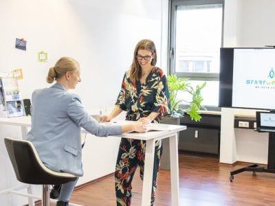 Büroraum mit zwei jungen Frauen an einem Besprecnhungstisch.