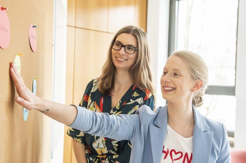 Zwei Frauen an der Pinnwand beim Projektmanagement